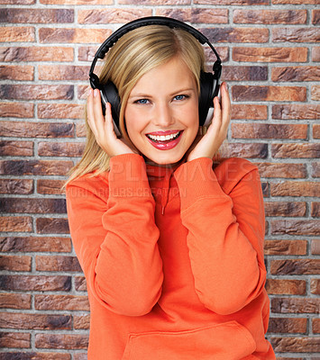 Buy stock photo Pretty blonde woman wearing headphones and listening to music