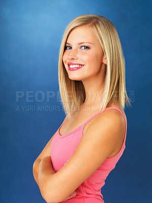 Buy stock photo Side view of pretty woman standing with arms folded against blue background