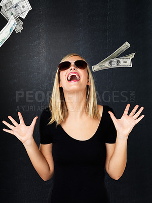 Buy stock photo Woman wearing sunglasses with her arms up in excitement as money falls around her