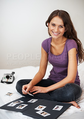 Buy stock photo Happy girl smiling while sitting on bed and choosing photographs for her album