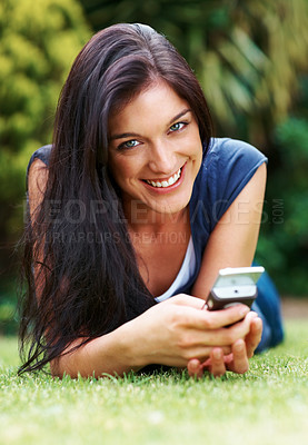 Buy stock photo Portrait of a cheerful young  lady with a mobile phone lying on grass - Outdoor