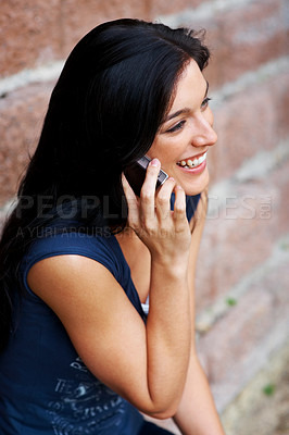 Buy stock photo Portrait of a smiling young woman speaking on cellphone against brick wall