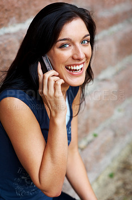 Buy stock photo Portrait of a charming young girl enjoying conversation on mobile phone against brick wall