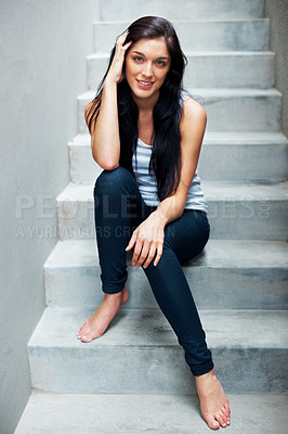 Buy stock photo Portrait of a pretty young female sitting casually on the staircase