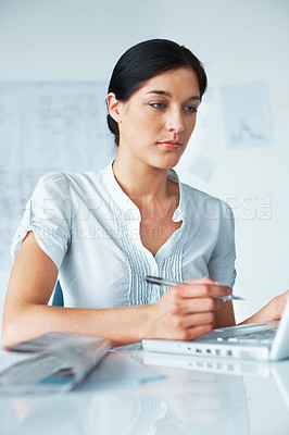 Buy stock photo Portrait of a confident young businesswoman taking notes while working on laptop in the office
