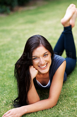 Buy stock photo Portrait of a smiling young girl relaxing on grass at the park - Outdoor
