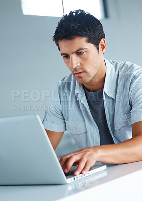 Buy stock photo Portrait of a handsome young man working on laptop