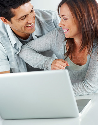 Buy stock photo Portarit of a smiling young couple enjoying themselves while using laptop
