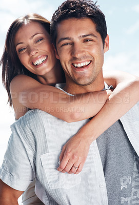 Buy stock photo Portrait of a joyful young man carrying girlfriend on his back - Outdoor