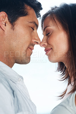Buy stock photo Portrait of a romantic young couple about to kiss each other