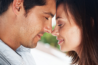 Buy stock photo Closeup portrait of a beautiful young couple with their heads together