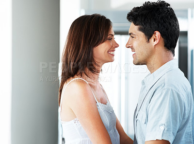 Buy stock photo Portrait of a lovely young couple looking at each other