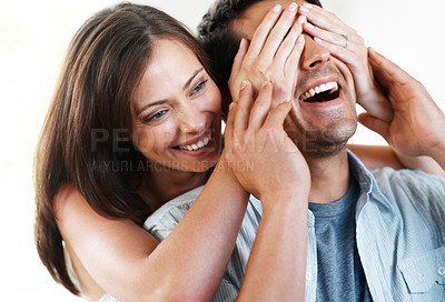 Buy stock photo Closeup portrait of a happy young female surprisng her husband by covering his eyes