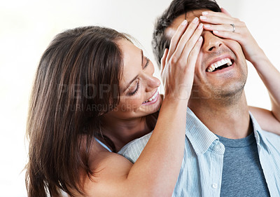 Buy stock photo Closeup portrait of a smiling young woman covering her husband eyes to surprise him