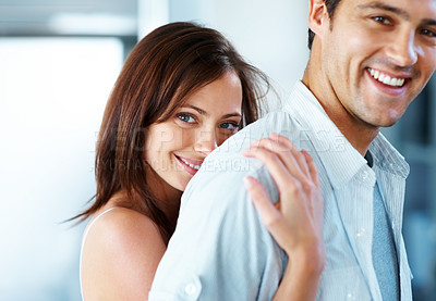 Buy stock photo Portrait of a beautiful young woman hugging her boyfriend from behind and smiling at you - copyspace