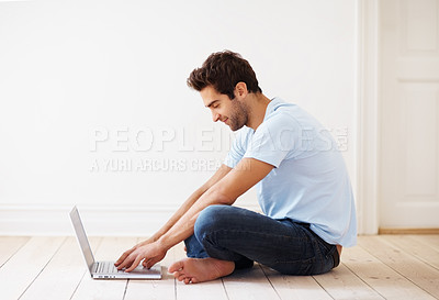 Buy stock photo Side view of man sitting on floor, working on laptop