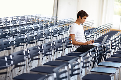 Buy stock photo Portrait of young man sitting alone in auditorium and working on laptop - Copyspace