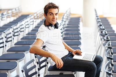 Buy stock photo Portrait of young man sitting alone in auditorium with a laptop and headphone