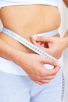 Buy stock photo Cropped image of a slim young woman measuring her waistline