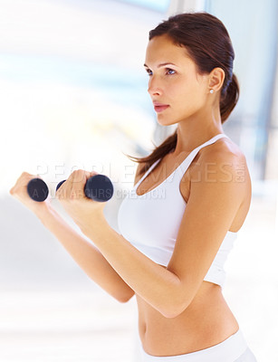 Buy stock photo Portrait of pretty young woman with a focused expression working out with free weights in gym