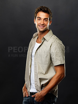 Buy stock photo Portrait of handsome guy standing with hands in pockets and smiling on black background