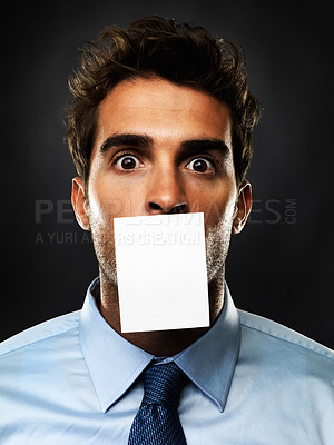 Buy stock photo Closeup portrait of business man in shock with a piece of paper covering his mouth on black background