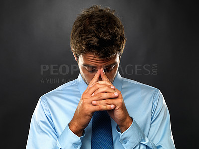 Buy stock photo Closeup of stressed business man with clasped hands looking down on black background