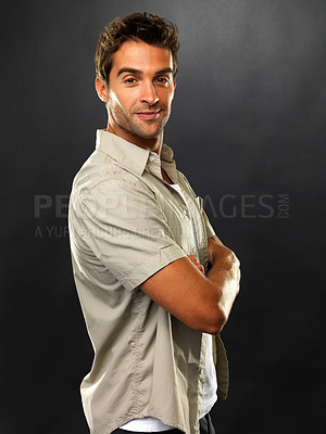 Buy stock photo Portrait of young man standing with arms crossed and smiling on black background