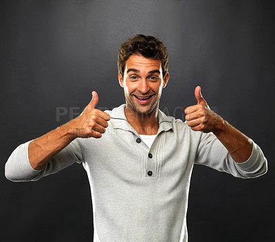 Buy stock photo Portrait of smart man smiling and giving you two thumbs up on black background