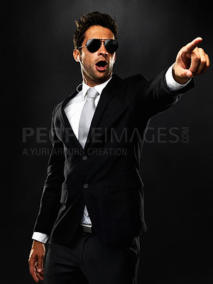 Buy stock photo Secret service agent pointing at someone on black background