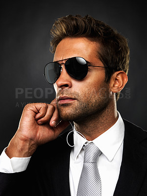 Buy stock photo Closeup of secret agent getting his instructions conveyed to him through earphones on black background