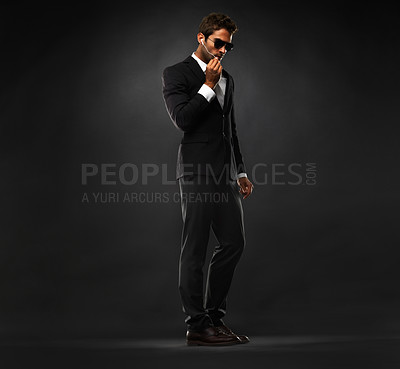Buy stock photo Full length of secret service agent having a conversation on his earphones against black background