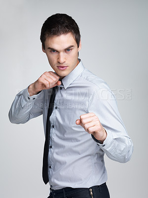 Buy stock photo Portrait of a confident young male entrepreneur ready for fight against grey background