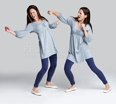 Buy stock photo Portrait of a psycho young woman fighting with herself against grey background