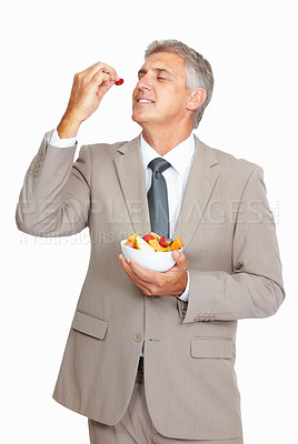 Buy stock photo Studio shot of a mature businessman eating a fruit salad against a white background