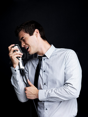 Buy stock photo Portrait of a successful young male star performer singing with old fashioned microphone against black background