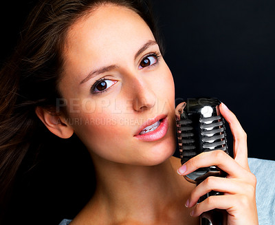 Buy stock photo Closeup portrait of a lovely young female jazz singer holding old fashioned microphone