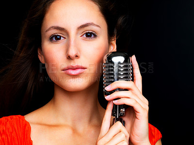 Buy stock photo Closeup portrait of a pretty young performer holding an old fashioned microphone