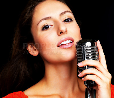 Buy stock photo an Closeup portrait of a cute young female jazz singer singing with old fashioned microphone