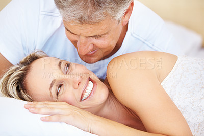 Buy stock photo Closeup of a mature couple giggling while sharing an intimate moment in bed in the morning