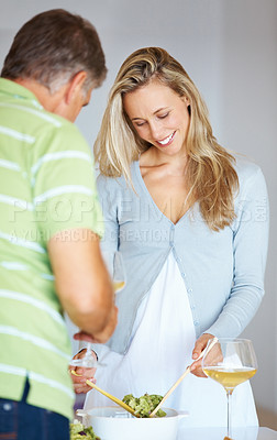 Buy stock photo Beautiful woman preparing salad with her husband in the kitchen at home