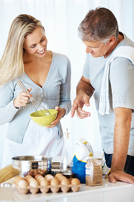 Buy stock photo Man helping woman to prepare batter with help of recipe book in kitchen at home