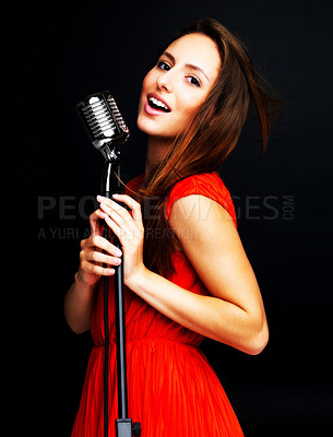 Buy stock photo An attractive young female jazz singer singing with an old fashioned microphone