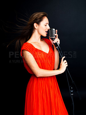 Buy stock photo Portrait of a pretty young female star singer singing with old fashioned microphone