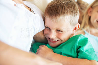 Buy stock photo Closeup of young boy smiling in his mother's arms