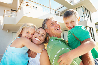 Buy stock photo Happy family smiling together outside their house