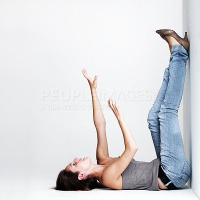 Buy stock photo Portrait of pretty young woman lying on floor with her legs up against a wall