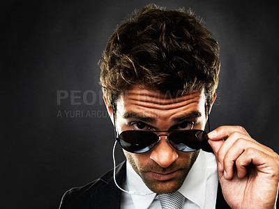 Buy stock photo Closeup portrait of secret agent lowering his sunglasses on black background