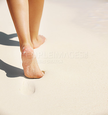 Buy stock photo Cropped closeup of a young woman's feet walking through sand on the beach leaving perfect footprints - copyspace