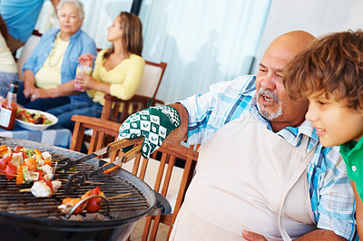 Buy stock photo Barbecuing - Old man and grandson preparing steak with family in the background